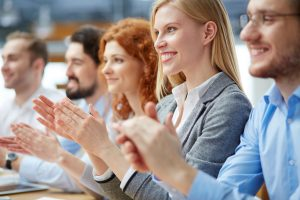 26806458 - photo of happy business people applauding at conference, focus on smiling blonde