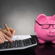 44311004 - close-up of businessperson with piggybank calculating tax at desk