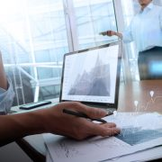 45551572 - business documents on office table with smart phone and laptop computer and graph business with social network diagram and two colleagues discussing data in the background