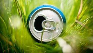 14859754 - opened blue aluminum can (bottle) laying in green grass, very shallow depth of field